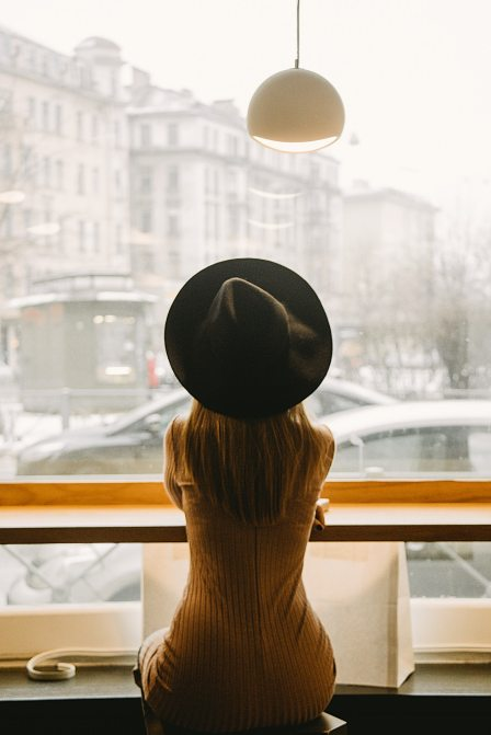 woman-in-black-hat-sitting-in-front-of-glass-window-3681653